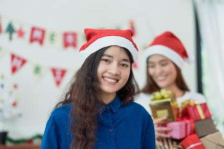 asia woman in xmas party holding group of present box with smiling face in christmas party,Holiday celebration in winter season,gift giving Stock Photo