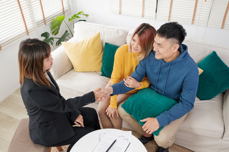 Asian couple sign home contract and handshake with realtor at living room in new home.buying new house real estate Stock Photo