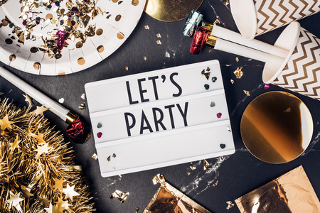 Let's party on light box with party cup,party blower,tinsel,confetti.Fun Celebrate holiday party time table top view.new year and christmas concept