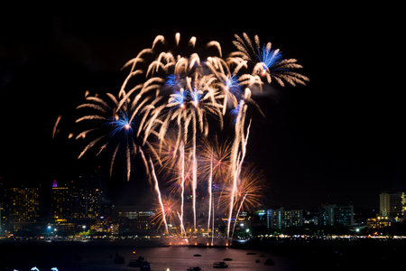 Fireworks explored over cityscape at night in sea port in Pattaya.Holiday festive celebration background Фото со стока