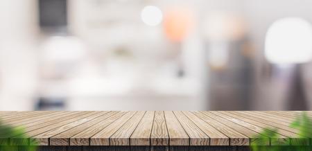 Mesa de tablón de madera marrón vacía con cocina casera borrosa con hoja de primer plano borrosa, plantilla de maqueta para exhibición o montaje de su diseño, pancarta para publicidad de producto, vista panorámica