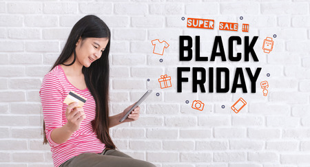 Asian woman in casual cloth holding credit card and using to online shopping in black friday sale with tablet at white brick wall.Digital technology lifestyle