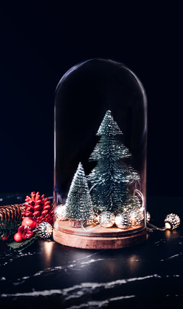 Merry Christmas with mistletoe and gift box icon with xmas tree and glowing light string and pine cone decoration on marble table and blue background