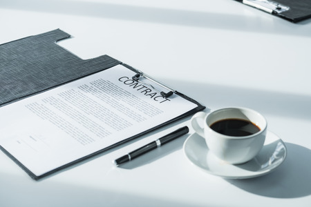Close up business contract paper on meeting room table with pen and coffee cup in sun light shadow with green plant at office,business agreement concept