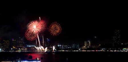 Fireworks explored over cityscape at night in sea port in Pattaya.Holiday festive celebration background Standard-Bild - 112242662