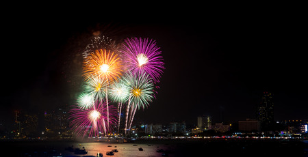 Fireworks explored over cityscape at night in sea port in Pattaya.Holiday festive celebration background Standard-Bild - 112242663