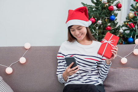Asia woman wear santa hat and holding gift box and use mobile chat with friend and sitting on sofa in christmas party,holiday celebration concept Standard-Bild - 112242680