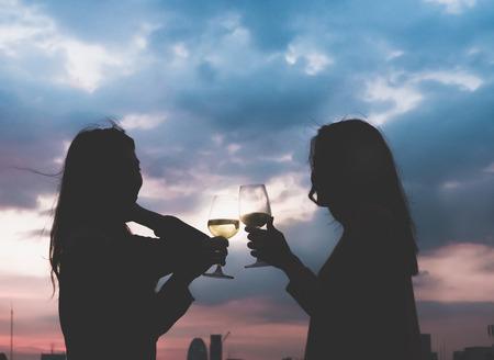 silhouette two asia lesbian lgbt couple toast champagne glass at rooftop party in sunset evening time,love wins,enjoy and cheerful lifestyle,birthday or anniversary party concept Standard-Bild - 112678544