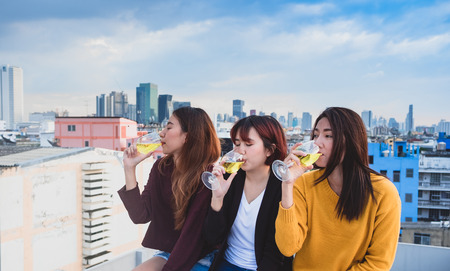 Happy group of asian girl friends enjoy laughing and cheerful sparkling wine glass at rooftop party,Holiday celebration festive,teeage lifestyle,freedom and fun Standard-Bild - 112678546