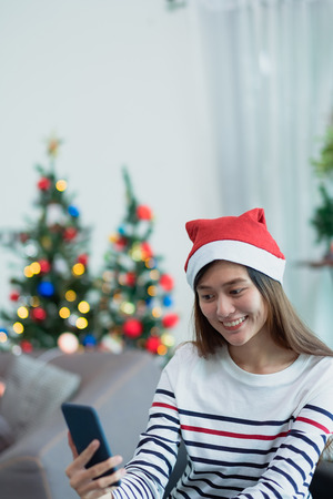 asia smile woman take selfie photo with mobile phone with blur christmas tree at xmas party,Live streaming video on social media event,Christmas holiday celebration party Standard-Bild - 112678548