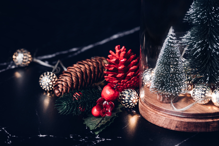 Christmas tree and glowing light string and pine cone and mistletoe decoration on marble table and blue background.Winter holiday greeting card Standard-Bild - 113445001