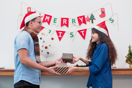 Gift giving for Christmas and new year,couple lover give present at xmas party,Holiday celebration concept Standard-Bild - 113445008