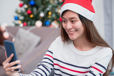 asia smile woman take selfie photo with mobile phone with blur christmas tree at xmas party,Live streaming video on social media event,Christmas holiday celebration party Standard-Bild - 113445012