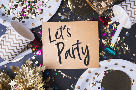 Let's party brush stroke handwriting on golden greeting card with party cup,party blower,tinsel,confetti.Holiday celebrate party time.top view tabletop Standard-Bild - 113445013
