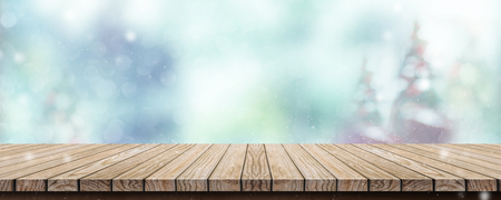 Wood table with abstract blur christmas tree and snow fall background with bokeh light.Mock up banner for display or montage of product Standard-Bild - 113445015