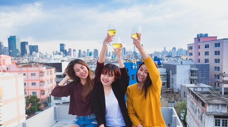 Happy group of asia girl friends enjoy laughing and cheerful toast sparkling wine glass at rooftop party,Holiday celebration festive,teenage lifestyle,freedom and fun Standard-Bild - 113445020