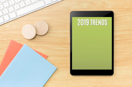2019 trends on green screen tablet with blue notebook and keyboard on wooden table,new year resolutions.Mock up for display your content Standard-Bild - 113445025