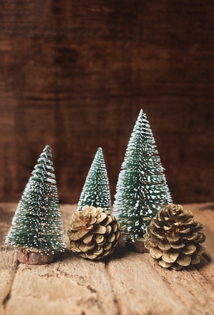 mini christmas tree and pine cone wood on rustic wooden table and dark brown hardwood wall.winter holiday seasonal greeting card.leave space to adding text or design Standard-Bild - 113445031