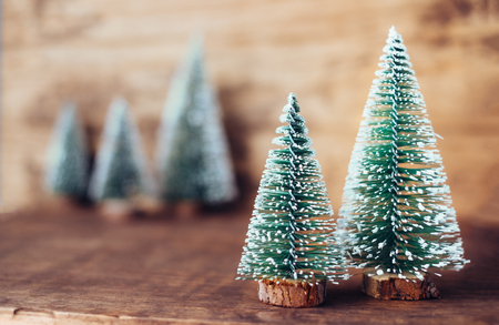 mini christmas tree wood on rustic wooden table and dark brown hardwood wall.winter holiday seasonal greeting card.leave space to adding text or design Standard-Bild - 113445052