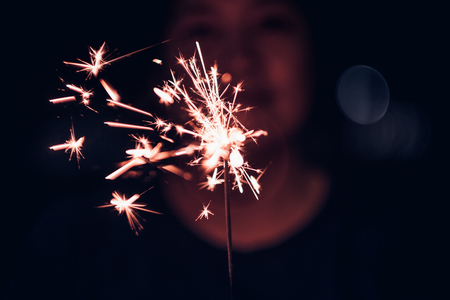 Hand holding burning Sparkler blast on a black background at night,holiday celebration event party,dark vintage tone Standard-Bild - 113445060