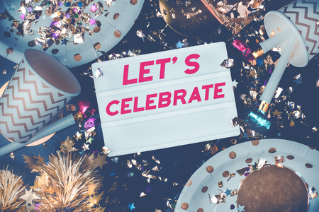 Lets celebrate on light box with party cup,party blower,tinsel,confetti.Fun Celebrate holiday party time table top view.new year and christmas concept Standard-Bild - 113445077