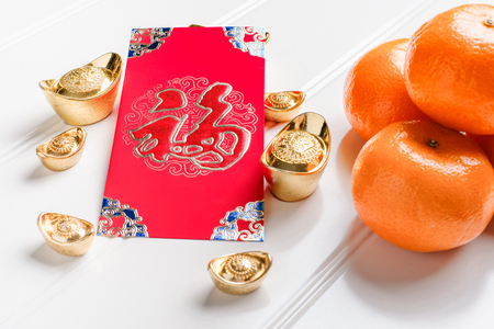 Top view Chinese New year red envelope packet ( ang pow ) with gold ingots and tangerine on white wood table top,Chinese Language on envelop mean Happiness and on ingot mean Wealthy Standard-Bild - 113445083