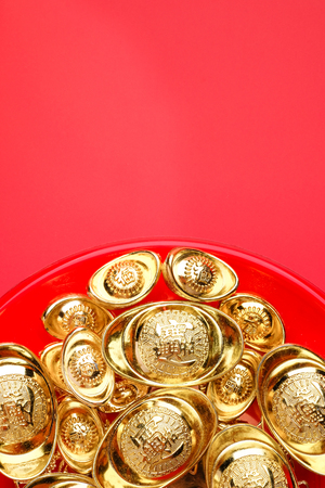 Top view group of golden ingots on red tray at red background.Chinese new year concept,leave space for adding text.Chinese Language on ingot mean wealthy Standard-Bild - 113445113