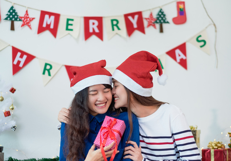 Asia lover Girlfriend kiss cheek and give Christmas gift at xmas party,Asia girl friends wear santa hat exchange red gift box with smiling face,gift giving,Lovely lesbian couple Standard-Bild - 113445115