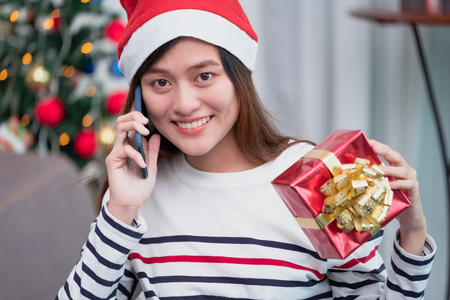 Asia woman wear santa hat and holding gift box and use mobile talk with friend and sitting on sofa in christmas party,holiday celebration concept Standard-Bild - 113445121
