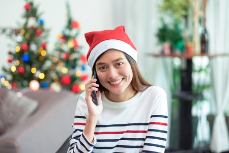 Asia woman wear santa hat and holding gift box and use mobile talk with friend and sitting on sofa in christmas party,holiday celebration concept Standard-Bild - 113445124