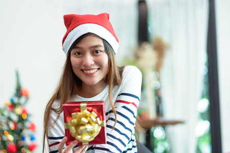 Asia woman smile holding gold xmas gift box at holiday party with decoration flag at background,present giving Christmas party present,winter holiday happiness moment. Standard-Bild - 113445126