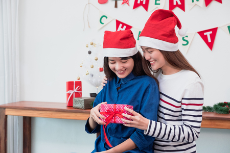 Asia girl friends wear santa hat in merry christmas party and exchange red gift box each other with smiling face,Xmas gift giving,Lovely lesbian couple Standard-Bild - 113445127