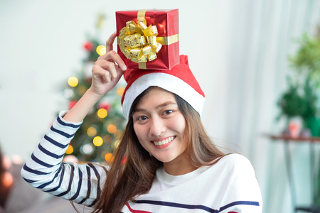 Asia woman smile holding gold xmas gift box at holiday party with decoration flag at background,present giving Christmas party present,winter holiday happiness moment. Standard-Bild - 113445128