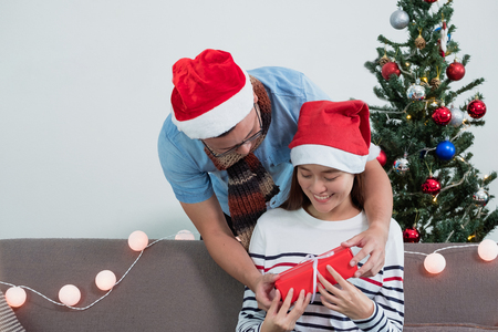 Asia lovers couple, boyfriend surprise girlfriendby giving Christmas present at sofa with xmas decoration tree at house party,Holiday celebrating season Standard-Bild - 113445129