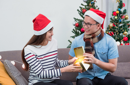 asian man open gold gift box with girlfriend on sofa at Christmas party,holiday celebration.surprise concept Standard-Bild - 113445132