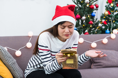 Asian woman upset when open gold xmas gift box at holiday party on sofa,boredom Christmas party present Standard-Bild - 113445134