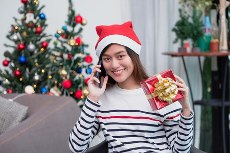 Asia woman wear santa hat and holding gift box and use mobile talk with friend and sitting on sofa in christmas party,holiday celebration concept Standard-Bild - 113445136
