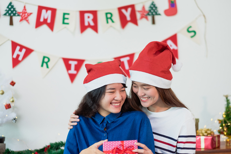 Asian lover Girl friend give Christmas gift at xmas party,Asia girl friends wear santa hat exchange red gift box with smiling face,gift giving,Lovely lesbian couple. Standard-Bild - 113445138