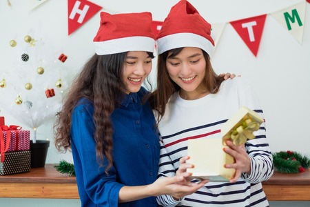 Asia girl friend open gold gift box together in christmas and new year party,Holiday celebration season event. Standard-Bild - 113445140