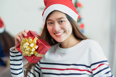 Asia woman smile holding gold xmas gift box at holiday party with decoration flag at background,present giving Christmas party present,winter holiday happiness moment Standard-Bild - 113445141