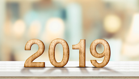 Happy new year 2019 on marble table with pale soft bokeh wall,banner for display or montage of product for holiday promotion and advertise for online content. Standard-Bild - 113445225