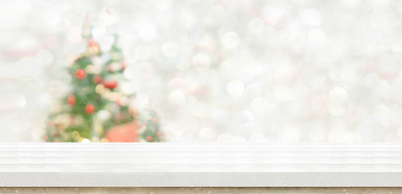 White marble table top at blur bokeh christmas tree decor with string light background when show falling,Winter holiday greeting card Standard-Bild - 113793794