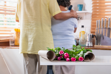 Close up pink rose with Asian Senior husband embrace wife while flower arrangement on table at kitchen at home in Valentine's Day.lovely senior couple concept