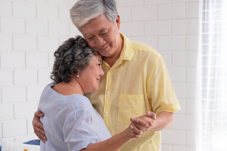 Happy Asian senior couple enjoy slow dancing at living room in house with warm love emotion.grandmother snuggle grandfather