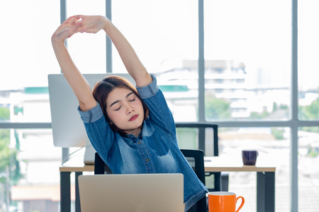 asian woman creative designer stretching arms up from working  with laptop  in modern office.take a break from work