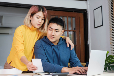 Asian couple together calculate home budget with paper bill and laptop in new house at table in kitchen