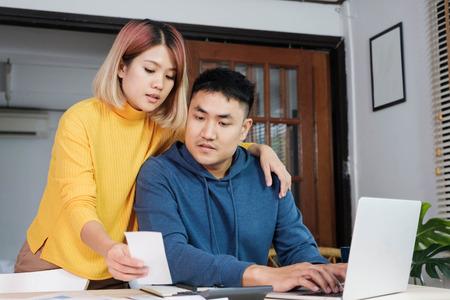 Un couple asiatique calcule ensemble le budget de la maison avec une facture papier et un ordinateur portable dans une nouvelle maison à table dans la cuisine Banque d'images