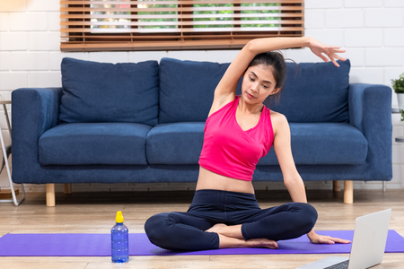 Asian woman use latpop  to training yoga pose online in living room floor at home.self learning