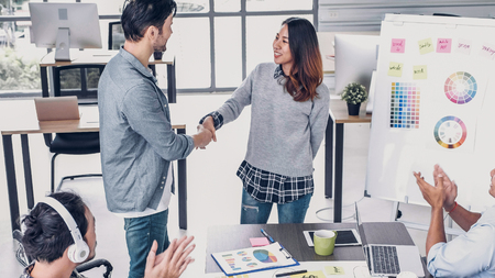 Female creative director boss handshake with designer and congratulation about getting promotion of job in modern creative office Standard-Bild - 118843612