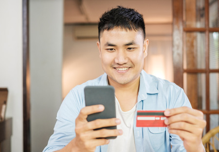 Asian man online shopping with credit card and mobile phone at home.digital lifestyle with technology Standard-Bild - 118844668